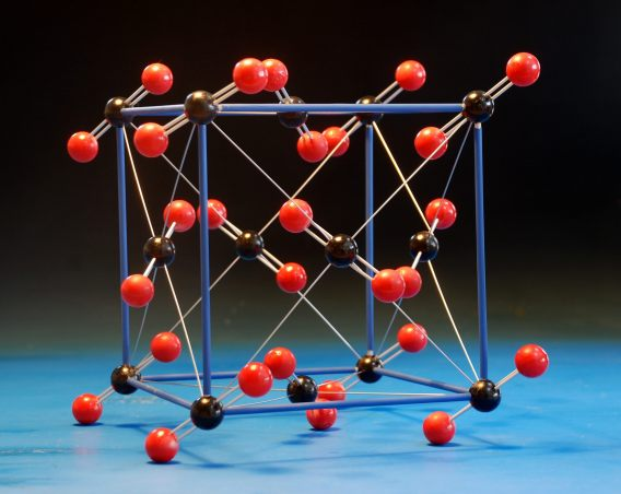 A large crystal structure model of carbon dioxide, CO2, made with wood balls and aluminium rods, with a highlighted unit cell