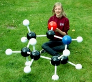 A girl sitting with a giant molecular model on a grass lawn